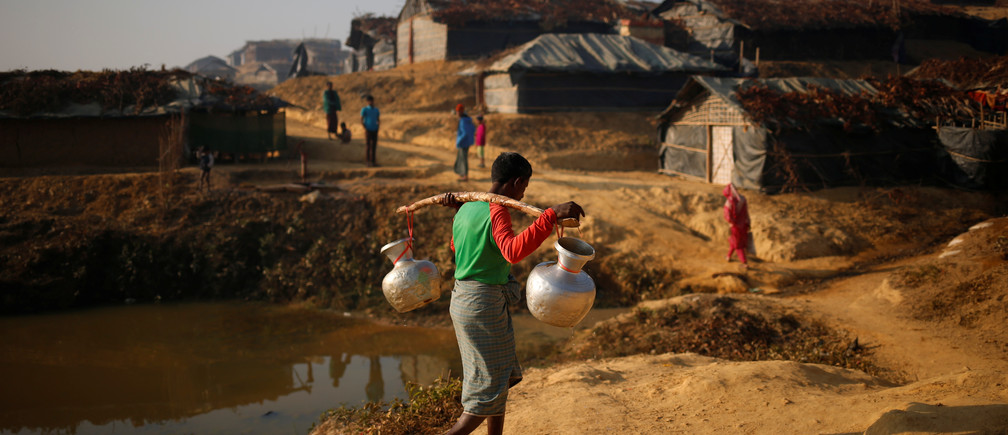 A Rohingya refugee man carries water on his shoulder in the morning at Kutupalang Unregistered Refugee Camp, in Cox's Bazar, Bangladesh, February 4, 2017. REUTERS/Mohammad Ponir Hossain - RTX2ZM7A