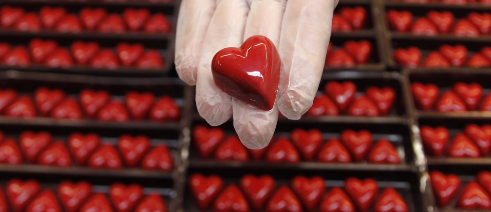 A worker displays a heart-shaped praline for Valentine's Day at a Wittamer chocolate boutique in Brussels February 14, 2012.