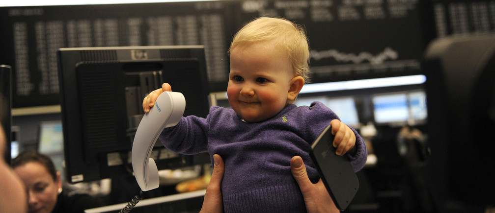 Eleven-month old toddler Vianne plays with a phone and a calculator as she sits on a traders desk in front of the German share price index DAX board at the German stock exchange in Frankfurt, February 20, 2009. Vianne and her mother visited a friend working as share trader at Frankfurt's stock exchange.  REUTERS/Kai Pfaffenbach (GERMANY) - BM2E52K1AUZ01