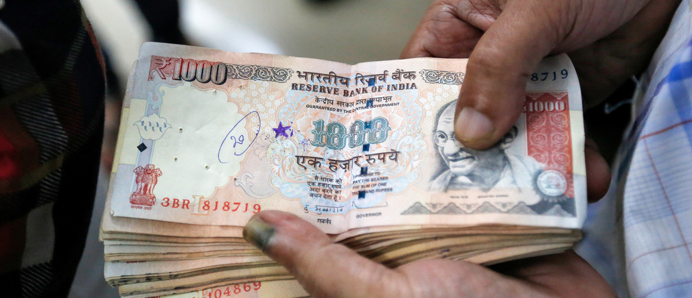 A customer waits to deposit 1000 Indian rupee banknotes in a cash deposit machine at bank in Mumbai, India, November 8, 2016. REUTERS/Danish Siddiqui - D1BEULRKGYAA