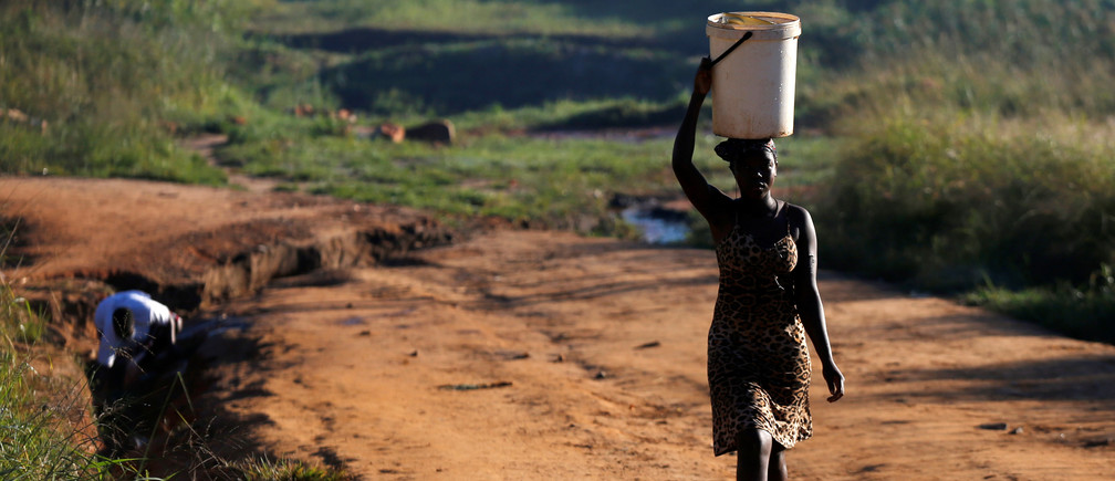 Women fetch water from a stream after Cyclone Idai in Chipinge, Zimbabwe, March 25,2019. REUTERS/Philimon Bulawayo - RC1AF83299C0