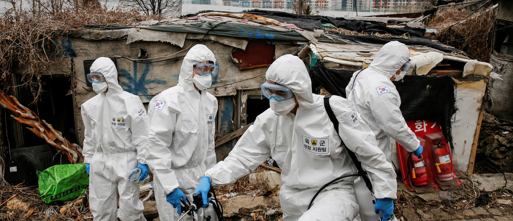 South Korean soldiers in protective gears sanitize shacks as a luxury high-rise apartment complex is seen in the background at Guryong village in Seoul, South Korea, March 3, 2020.