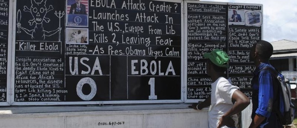 "Bystanders read headlines saying ""Ebola 1: USA 0"" at the Daily Talk, a street side chalkboard newspaper, in Monrovia October 16, 2014. REUTERS/James Giahyue (LIBERIA - Tags: HEALTH DISASTER MEDIA TPX IMAGES OF THE DAY) - GM1EAAH04JD01"