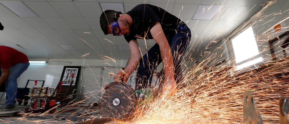 Syrian refugee metal shop trainees work at one of the vocational training centres of The Norwegian Refugee Council (NRC) at Azraq refugee camp near Al Azraq city, Jordan, June 27, 2016. REUTERS/Muhammad Hamed - S1AETMIJSSAA