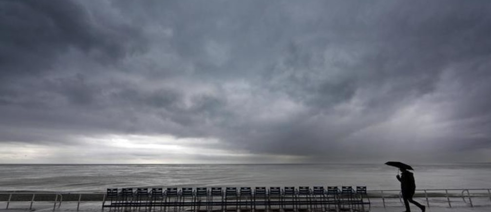 A man walks under an umbrella on the Promenade Des Anglais in Nice while heavy rain hits southern France November 25, 2014.  REUTERS/Eric Gaillard (FRANCE - Tags: ENVIRONMENT)