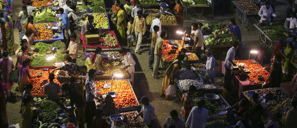 Vendors use solar powered lights at an open air evening market as customers buy fruits and vegetables in the western Indian city of Ahmedabad September 10, 2009. When night falls in remote parts of Africa and the Indian subcontinent, hundreds of millions of people without access to electricity turn to candles or flammable and polluting kerosene lamps for illumination. Slowly through small loans for solar powered devices, microfinance is bringing light to these rural regions where a lack of electricity has stymied economic development, literacy rates and health. Picture taken Sepetember 10, 2009. To match feature INDIA-SOLAR/  REUTERS/Amit Dave (INDIA ENERGY BUSINESS AGRICULTURE) - GM1E5AR0L7B01