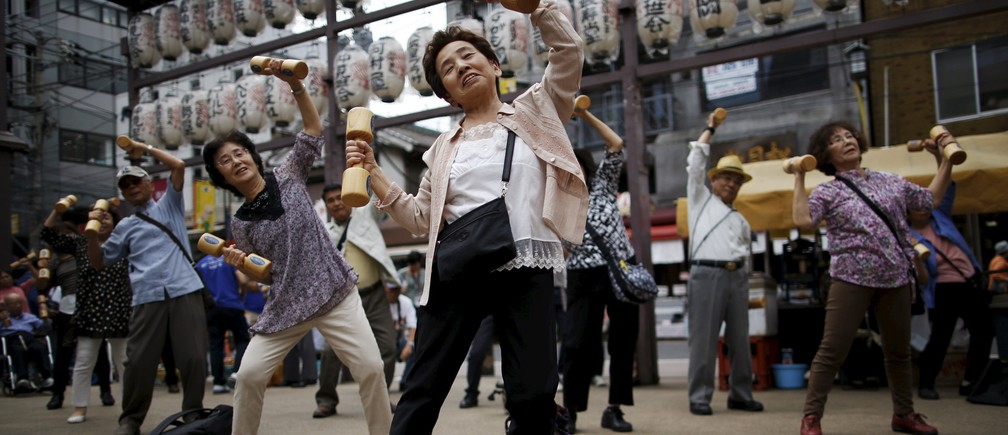"Elderly and middle-age people exercise with wooden dumbbells during a health promotion event to mark Japan's ""Respect for the Aged Day"" at a temple in Tokyo's Sugamo district, an area popular among the Japanese elderly, September 21, 2015."