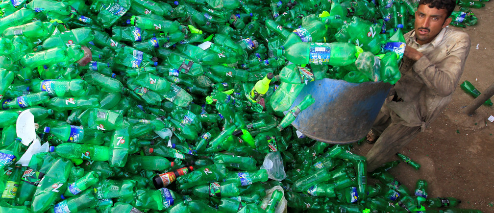 A worker picks up bottles to throw in a plastic bottle chipper at a recycling workshop in Pakistan