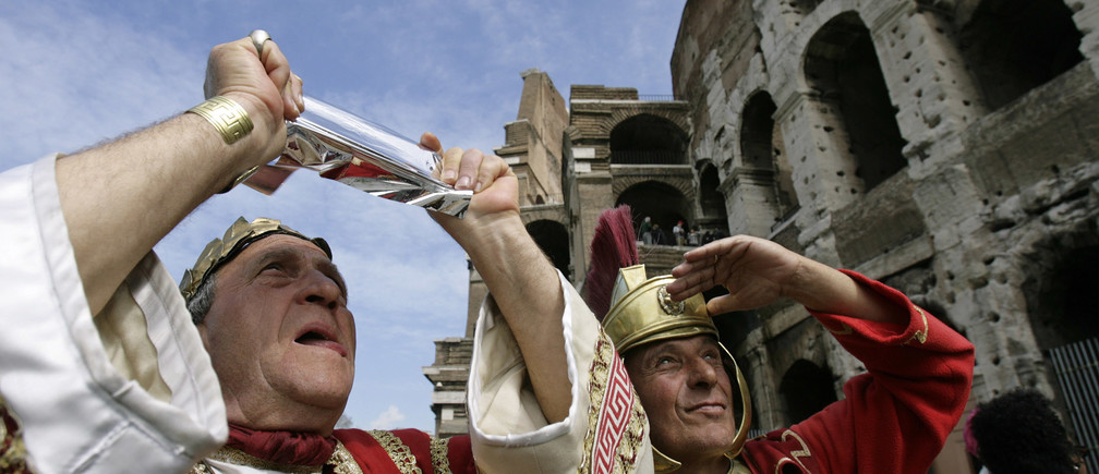 A pair of Italian men dressed as a former Roman emperor and gladiator, who make their living posing with tourists, use a special filter to view a partial eclipse of the sun outside the Colosseum in Rome March 29, 2006.   REUTERS/Chris Helgren - GM1DSGPXDHAA