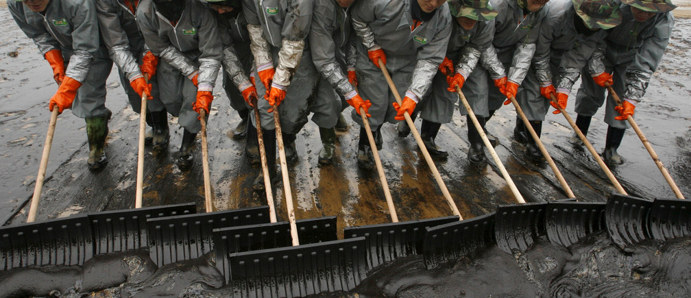 Soldiers from the South Korean army make efforts to remove crude oil spills over Mallipo swimming beach after after an accident involving Hong-Kong registered oil tanker Hebei Spirit in Taean, about 170km (106 miles) southwest of Seoul, December 10, 2007. South Korea on Monday was tallying the environmental and economic cost of the worst oil spill in its history as thousands of workers struggled to protect an area known for its nature reserve and vibrant marine economy.  REUTERS/Jo Yong-Hak (SOUTH KOREA) - GM1DWTZOQAAA