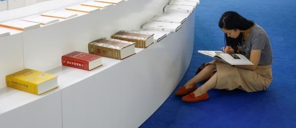 A woman reads a book at the Beijing International Book Fair in Beijing, China, August 23, 2017.   REUTERS/Thomas Peter