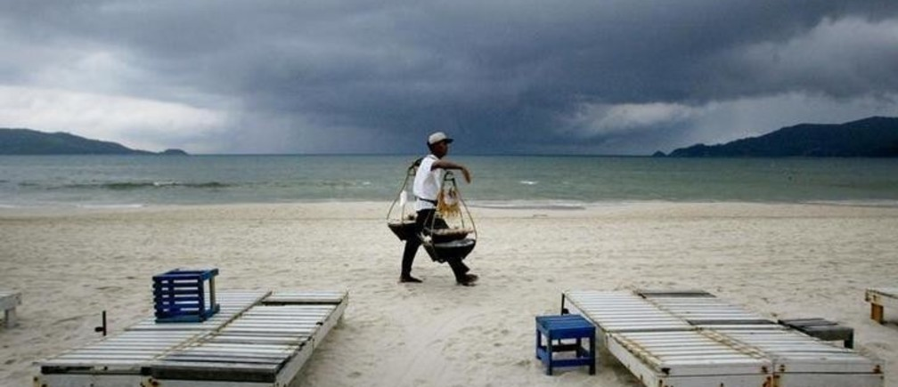 A Thai food vendor strolls past empty beach chairs as a storm approaches Patong Beach on the Southern Thai resort island of Phuket October 31, 2002.Thailand reassured tourists on Thursday that the country was safe despitewarnings from western nations such as Britain which said on Tuesday threatsto westerners on Phuket island had increased sharply. Phuket relies heavilyon the tourist trade and economists say a major fall in tourist arrivalswould slice a large chunk off Thailand's foreign exchange earnings and throwmillions of people out of work. NO RIGHTS CLEARANCES OR PERMISSIONS ARE REQUIRED FOR THIS IMAGE  REUTERS/Jason ReedJIR/JS
