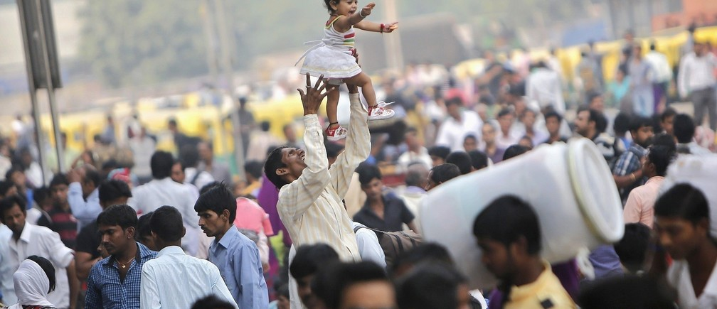 """A passenger plays with his child while waiting to enter a crowded railway station ahead of the Hindu religious festival """"Chhat Puja"""", in New Delhi October 24, 2014. Hindu devotees worship the Sun god and fast all day for the betterment of their family and society during the festival."""