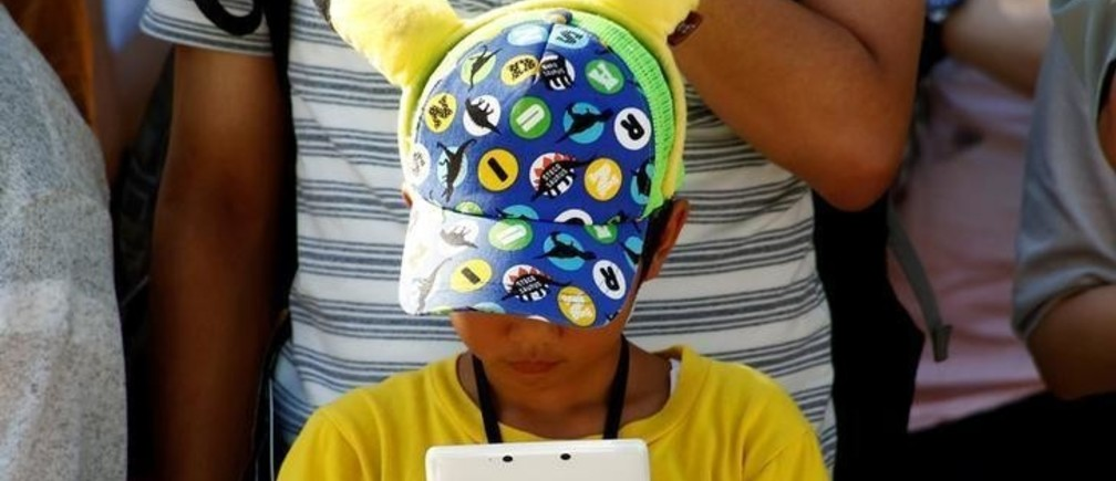 A boy plays Nintendo's game console prior to a parade where Pokemon's character Pikachu attends, in Yokohama, Japan, August 7, 2016. Picture taken on August 7, 2016. REUTERS/Kim Kyung-Hoon