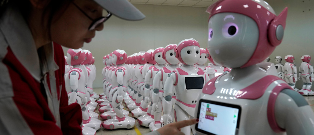 A worker puts finishing touches to an iPal social robot, designed by AvatarMind, at an assembly plant in Suzhou, Jiangsu province, China July 4, 2018. Designed to offer education, care and companionship to children and the elderly, the 3.5-feet tall humanoid robots come in two genders and can tell stories, take photos and deliver educational or promotional content. Picture taken July 4, 2018.REUTERS/Aly Song - RC1B1450D2B0