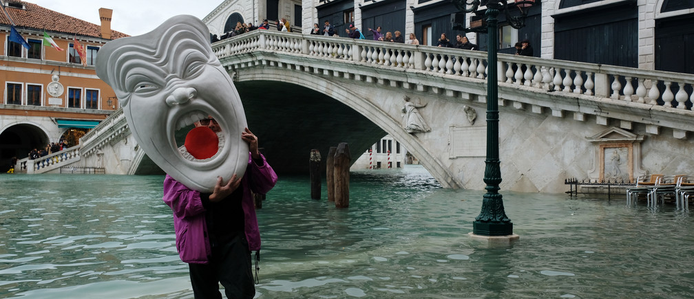 A man with a mask walks in a flooded street during a period of seasonal high water in Venice, Italy, November 17, 2019. REUTERS/Manuel Silvestri - RC22DD9Y2EU8