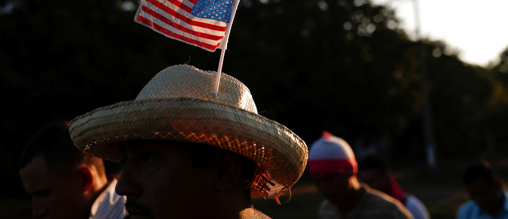 A migrant from Honduras, part of a caravan traveling to the U.S., wears a hat with the U.S. flag while he walks along the road to Huixtla, near Tapachula, Mexico, October 31, 2018. REUTERS/Carlos Garcia Rawlins - RC14FAA773D0