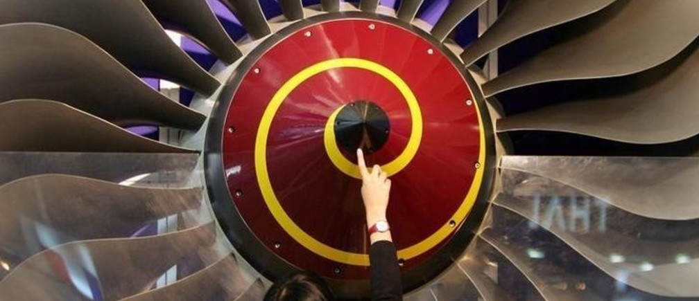 """A Chinese visitor touches a Rolls-Royce swept fan on display at the """"Aviation Expo China 2005"""" in Beijing September 22, 2005. Rolls-Royce Group Plc. is taking an even keener interest in China than most western exporters, because of the country's taste for the big airliners that the British company specialises in supplying engines for. The company, the second-largest aero-engine maker, sees the country's aviation industry not only growing unusually fast over the coming 20 years but putting an emphasis on wide-body planes. REUTERS/Claro Cortes IV  CC/JJ"""