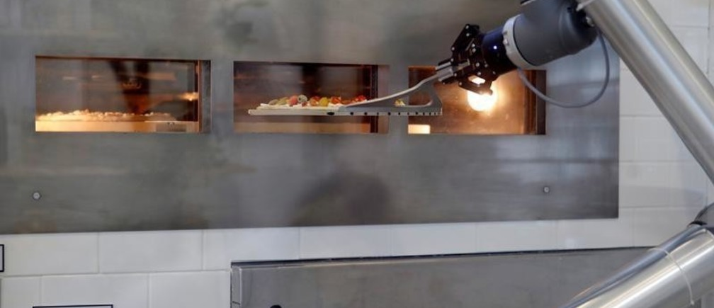 A pizzaiolo robot prepares a pizza before the customer's eyes at the showroom of French food startup EKIM in Montevrain near Paris, France, June 26, 2018. Picture taken June 26, 2018.  REUTERS/Philippe Wojazer - RC1D8E0CE100