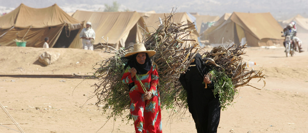 Women carry firewood in al-Mazraq refugee camp near the northwestern Yemeni province of Saada November 12, 2009. Around 8,000 people live in the camp near the Saudi border, after they fled battles raging between the army and Shi'ite rebels in northern Yemen for the past three months. REUTERS/Khaled Abdullah (YEMEN CONFLICT POLITICS) - GM1E5BC1U2O01