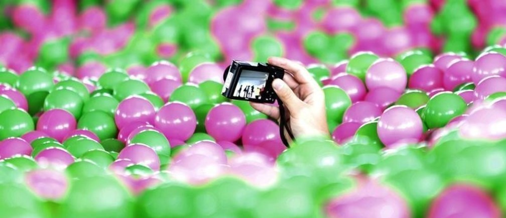 """A participant takes pictures with a camera in a swimming pool filled with pink and green plastic balls during a Guinness World Records attempt of the Largest Ball Pit as part of the """"Pink October"""" campaign at Kerry Hotel in Pudong, Shanghai October 30, 2013. The event, aimed at raising awareness of breast cancer prevention, set the world record with one million balls in the 25-metre-long (82 ft.) and 12.6-metre-wide (41 ft.) swimming pool, according to local media.  REUTERS/Aly Song (CHINA - Tags: SOCIETY HEALTH) - GM1E9AU19IY01"""