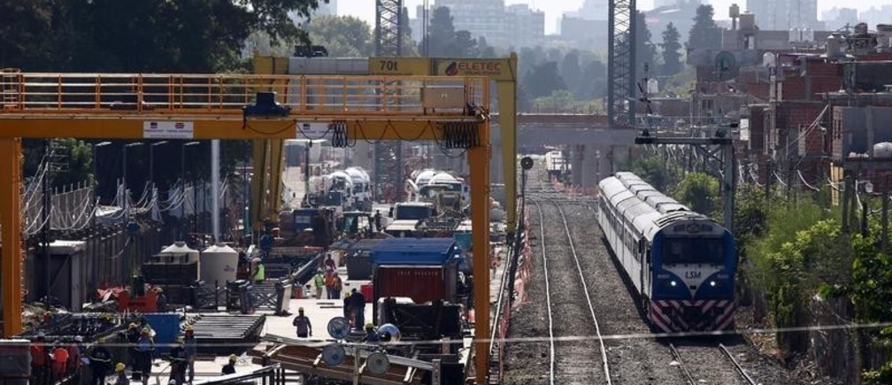 Employees work next to railroad tracks as a train passes by in Buenos Aires, Argentina, March 13, 2018.