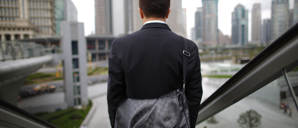 A business man rides an escalator in the financial district of Pudong in Shanghai September 21, 2011. REUTERS/Aly Song (CHINA - Tags: CITYSPACE SOCIETY) - RTR2RVU1