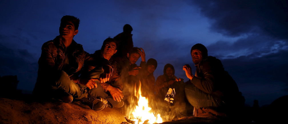 Migrants who are waiting to cross the Greek-Macedonian border, sit by the fire near the village of Idomeni, Greece, March 3, 2016. REUTERS/Marko Djurica - GF10000332225