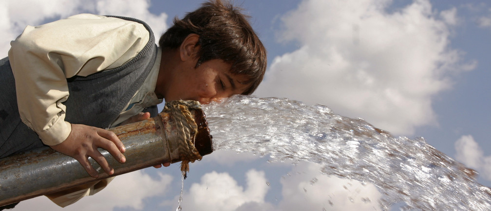 A boy drinks from a water pump in a village near the Yemeni capital, Sanaa.