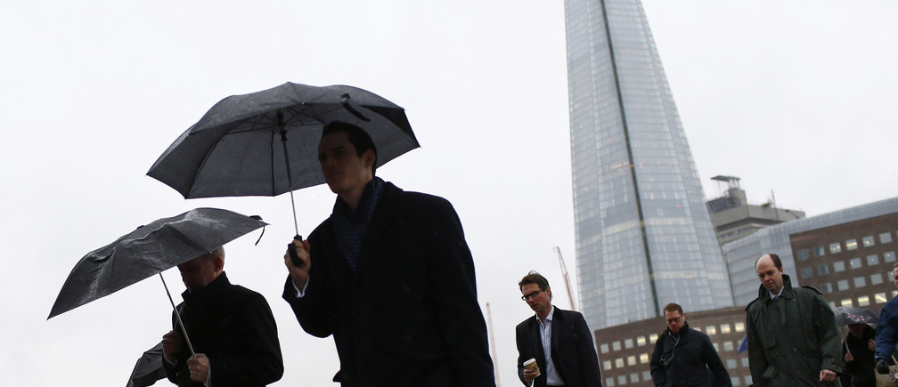 The Shard is seen as workers use umbrellas to shelter themselves from the rain while crossing London Bridge in London February 28, 2014.