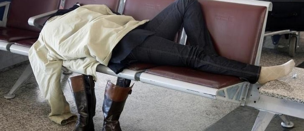 A passenger sleeps on a bench at the Fiumicino International airport in Rome November 11, 2008. Dozens of Alitalia flights were cancelled for a second day on Tuesday after protests by airline staff opposed to a takeover by a business consortium had forced the cancellation of about 100 flights on Monday, with the government threatening tough action against the strikers.  REUTERS/Max Rossi   (ITALY)