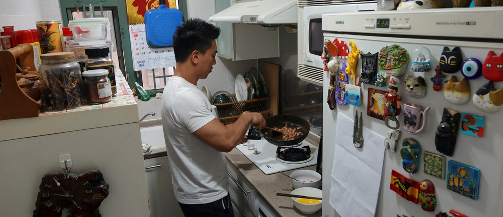 Fitness trainer Mike Lee demonstrates making a dish with plant-based meat Omnipork for the camera at his home in Hong Kong, China April 20, 2020. Picture taken April 20, 2020. REUTERS/Joyce Zhou - RC2C9G9WSI3Q