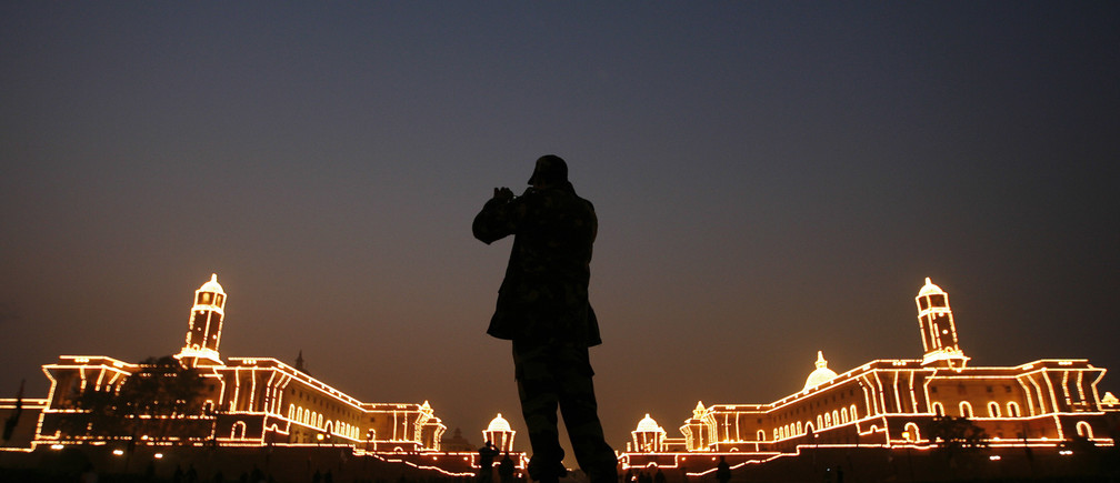 "An Indian soldier takes pictures of illuminated Indian Defence Ministry (L) and Home Ministry buildings during a rehearsal for the ""Beating the Retreat"" ceremony in New Delhi January 24, 2010. The ceremony, held every year on January 29, marks the official end of the Indian Republic Day celebrations. REUTERS/Adnan Abidi (INDIA - Tags: MILITARY CITYSCAPE SOCIETY ANNIVERSARY IMAGES OF THE DAY) - GM1E61O1NKN01"