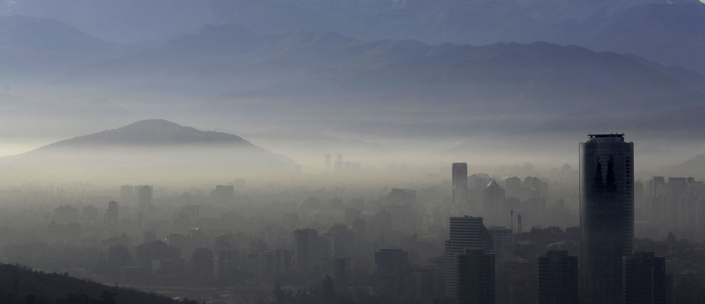 Smog shrouds Chile's capital Santiago, June 22, 2015. Chilean authorities declared an environmental emergency for the Santiago metropolitan region for Monday, forcing more than 900 industries to temporarily shut down and about 40 percent of the capital's 1.7 million cars off the roads. The emergency, the first since 1999, will be in place for 24 hours and can be extended further if authorities deem conditions have not improved. REUTERS/Ueslei Marcelino      TPX IMAGES OF THE DAY      - GF10000135995