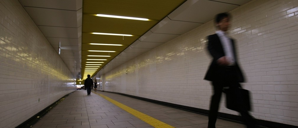 A businessman walks through a station in Tokyo June 27, 2008.   REUTERS/Yuriko Nakao (JAPAN) - RTX7DXL