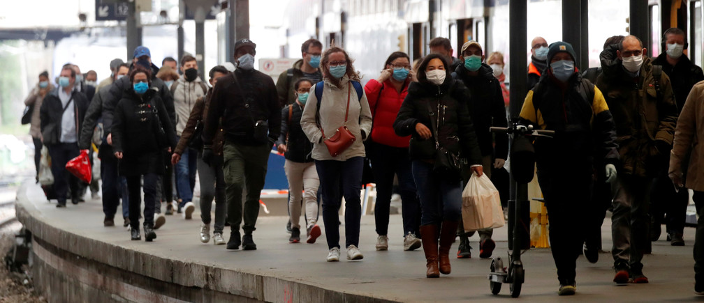 Commuters, wearing protective face masks, walk on a platform at the Saint-Lazare train station in Paris, on the first day mask usage is mandatory in public transport, after France begun a gradual end to a nationwide lockdown due to the coronavirus disease (COVID-19) in France, May 11, 2020. REUTERS/Charles Platiau - RC28MG9KZ9YB