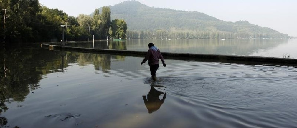 A man wades through a flooded road along the banks of Dal Lake in Srinagar September 18, 2014. Both the Indian and Pakistani sides of the disputed Himalayan region have seen extensive flooding this month with Srinagar particularly hard hit. Hundreds of people have been killed and tens of thousands are homeless. REUTERS/Danish Ismail (INDIAN-ADMINISTERED KASHMIR - Tags: DISASTER ENVIRONMENT) - GM1EA9I1A0701