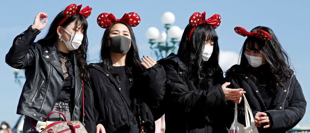 Visitors wearing protective face masks and Minnie Mouse costumes, following an outbreak of the coronavirus, are seen outside Tokyo Disneyland in Urayasu, east of Tokyo, Japan February 28, 2020.  REUTERS/Issei Kato - RC2I9F9NBW63