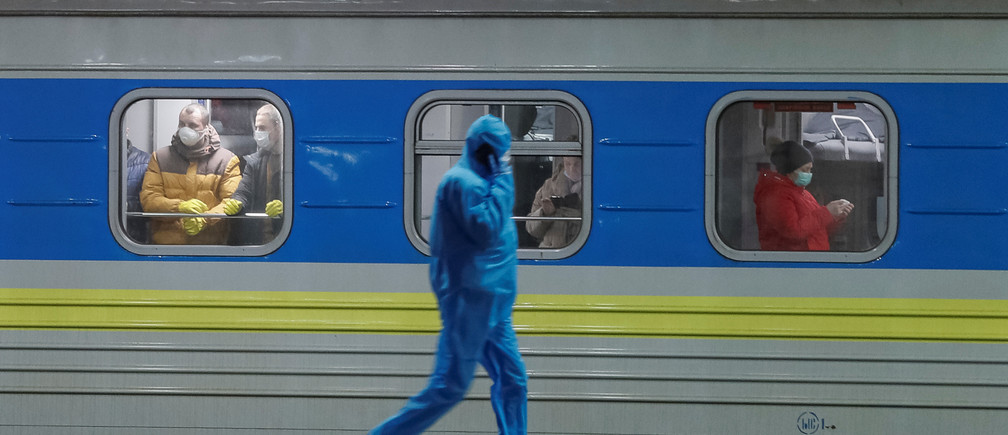 An employee wearing a protective suit walks past the train which evacuated Ukrainian citizens from Latvia due of the spread of the coronavirus disease (COVID-19), at the central railway station in Kiev, Ukraine March 23, 2020.  REUTERS/Gleb Garanich - RC2WPF9P1RI5