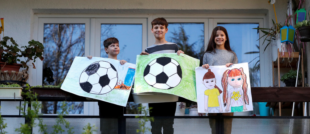"Ivan Posta, 8, Vince Posta, 11, and Vilma Posta, pose for a photograph while holding pictures that they drew during the Coronavirus disease (COVID-19) outbreak, while standing on the balcony at their home in Budapest, Hungary, April 10, 2020. Ivan drew a soccer ball, ""because, I like to play football with friends."" Vince also drew a soccer ball ""because we can't play football in the garden as there are trees and bushes everywhere."" Vilma drew her friends and said she missed her friends the most. ""I'm fine, only teachers give too many lessons,"" she added. REUTERS/Bernadett Szabo      SEARCH ""CORONAVIRUS DRAWING"" FOR THIS STORY. SEARCH ""WIDER IMAGE"" FOR ALL STORIES. - RC2BAG91EKM3"