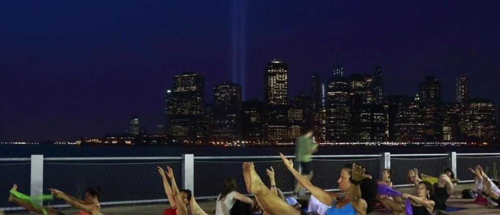Instructor Lou Cornacchia (C) leads a pilates class on Pier 5 at Brooklyn Bridge Park as the Tribute in Lights illuminates the sky over Lower Manhattan on the 12th anniversary of the 9/11 attacks in New York September 11, 2013. Bagpipes, tolling bells and a reading of the names of the nearly 3,000 people who died when hijacked jetliners crashed into the World Trade Center, the Pentagon, and a Pennsylvania field marked the 12th anniversary of the September 11 attacks in 2001.   REUTERS/Brendan McDermid (UNITED STATES  - Tags: DISASTER ANNIVERSARY CITYSCAPE) - GM1E99C0QDW01