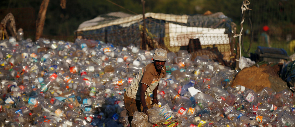 A man collects waste materials including plastic bottles to be recycled at an informal settlement in Kliptown, Soweto, South Africa, February 27, 2019. REUTERS/Siphiwe Sibeko - RC11D7E07E50