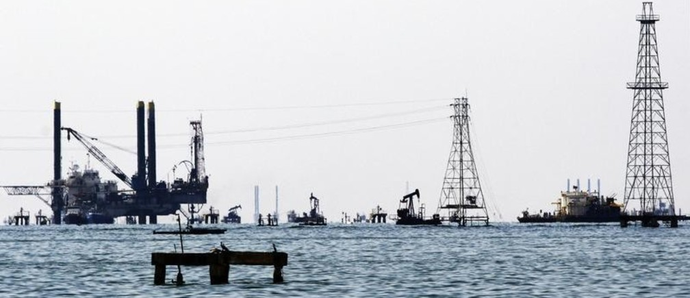 Oil rigs and platforms are seen at Maracaibo's lake near the western city of Maracaibo January 2, 2008. Oil vaulted to a record $100 a barrel on Wednesday as violence in Nigeria, tight energy stockpiles and a weaker dollar triggered a surge of speculative buying, dealers said. REUTERS/Isaac Urrutia (VENEZUELA) - GM1DWYLFIRAA