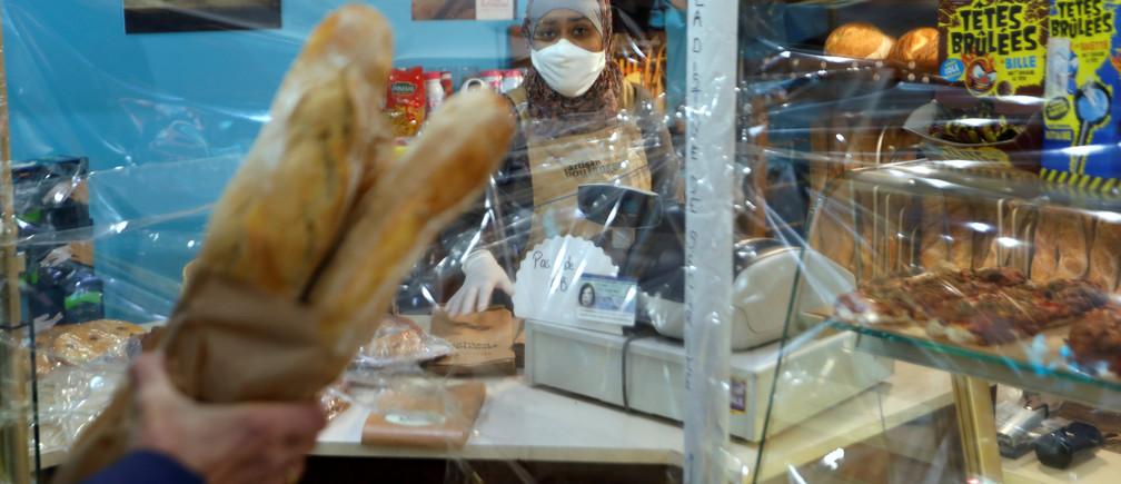 Un residente sostiene baguettes francesas después de haberlas metido por un agujero en una protección de plástico en una panadería en Fontenay-sous-Bois cerca de París durante el brote de la enfermedad del Coronavirus (COVID-19) en Francia, el 15 de abril de 2020.