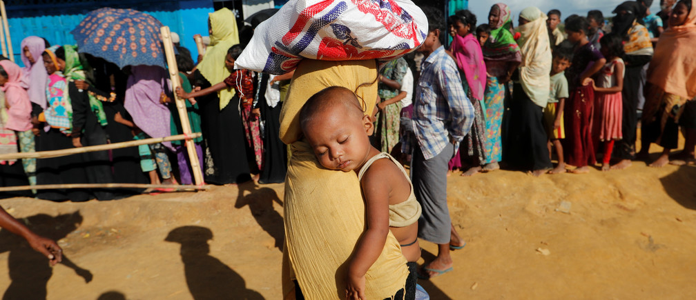 A Rohingya refugee woman walks carrying her baby after receiving food aid in a camp near Cox's Bazar, Bangladesh October 10, 2017. REUTERS/Jorge Silva - RC11B891C8C0