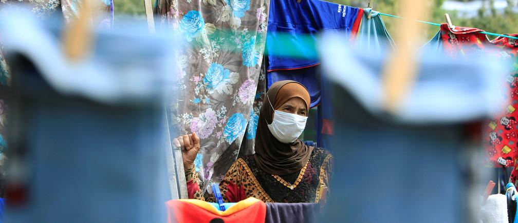 Una mujer refugiada siria que lleva una máscara facial cuelga la ropa para que se seque, mientras el Líbano extiende un encierro de dos semanas para combatir la propagación de la enfermedad coronavirus (COVID-19) en un campamento de refugiados sirios en la aldea de Ketermaya, Líbano 26 de marzo de 2020.