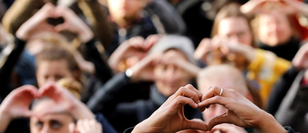 People make hearts with their fingers during a ceremony outside the Bourse, commemorating the first anniversary of the bomb attacks in Brussels metro and the Belgian international airport of Zaventem, in Brussels, Belgium, March 22, 2017.