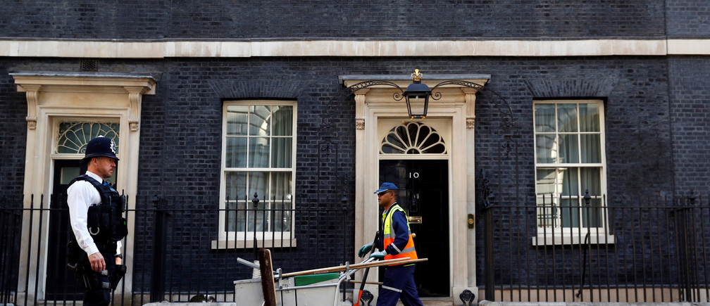 A police officer and a street cleaner walk past 10 Downing Street, in central London, Britain June 15, 2017. REUTERS/Phil Noble - RC1EC1ECD900