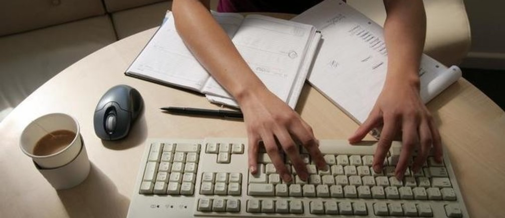 A generic picture of a woman working in an office sitting at her desk typing on a computer. REUTERS/Catherine Benson  CRB