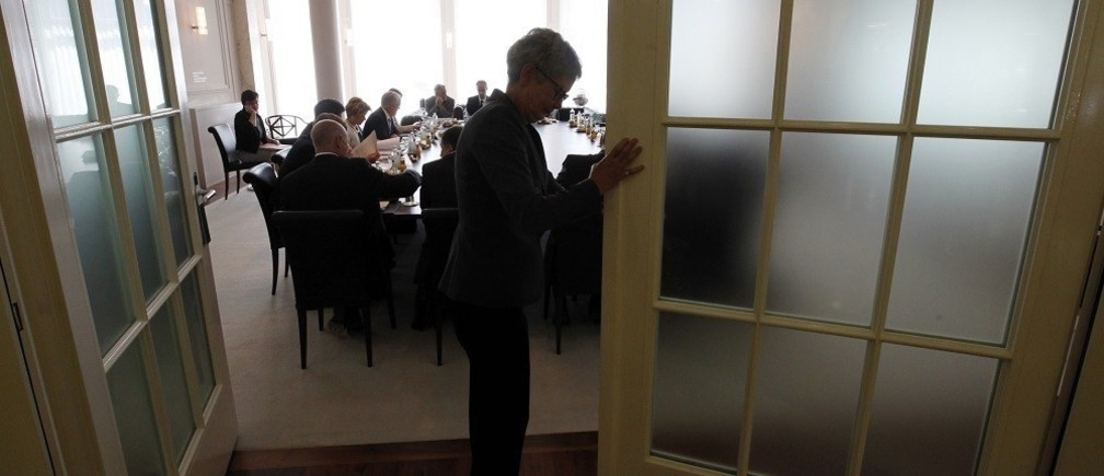 A clerk closes the door before a round table talk on the shifting of lower import prices to customers due to the strong Swiss franc in Bern August 10, 2011.REUTERS/Pascal Lauener (SWITZERLAND - Tags: POLITICS BUSINESS) - RTR2PS81